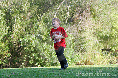 Boy happily runs at park