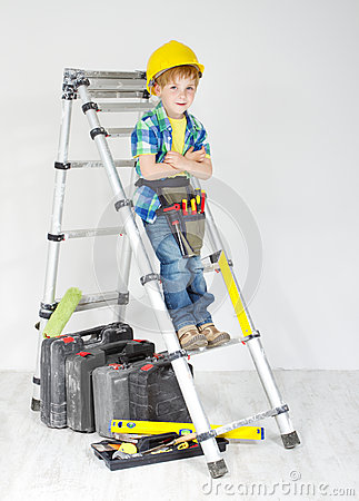 Boy with helmet and tool belt on stepladder