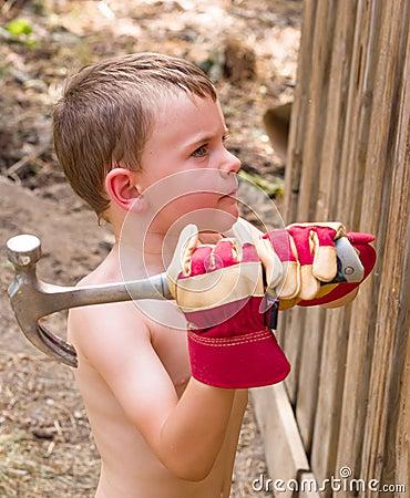 Boy helping build fence