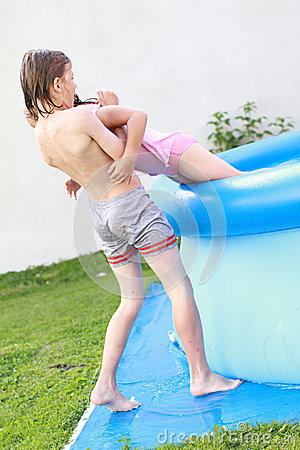 Boy helping a girl get out from a pool