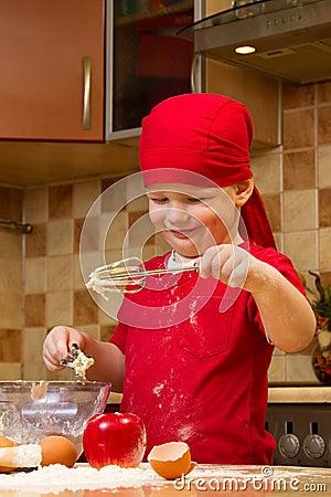 Boy helping at kitchen with baking pie