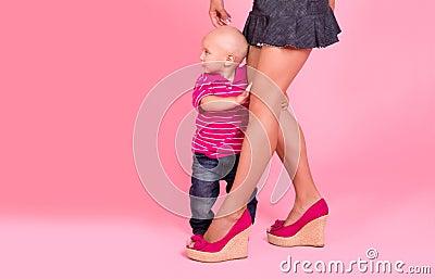 Boy hides behind mom feet