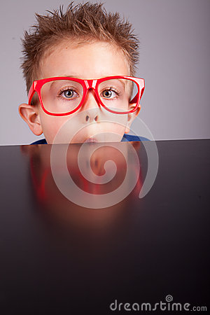 Boy hiding behind a table