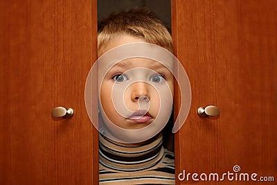 Boy is hiding in wardrobe
