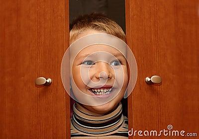 Boy is hiding in a wardrobe