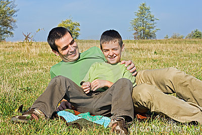 Boy and his father laying outside