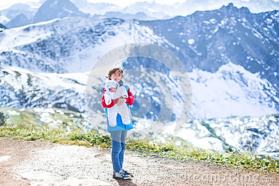 Boy with his newborn baby brother in mountains