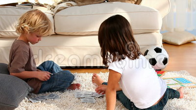 Boy and his sister playing cards Stock Photo
