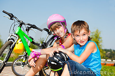 Boy and his sister in protective cycling helmets