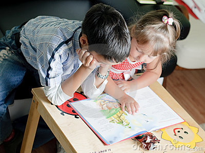 A boy and his sister are reading a book