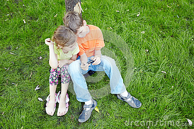 Boy and his sister sit and look at screen of phone