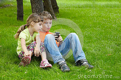 Boy and his sister sit and play electronic game