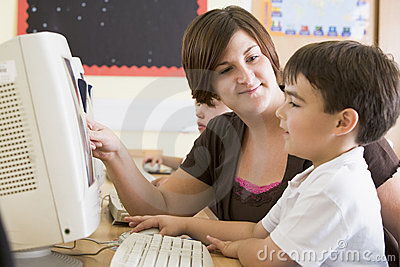 A boy and his teacher working on a computer