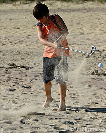 Boy hits a golf ball at the beach