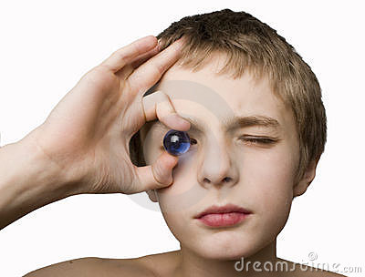 Boy holding blue marble to eye