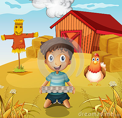 A boy holding an empty egg tray at the farm with a scarecrow