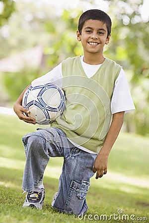 Boy holding football in park