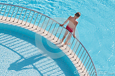 Boy holding the handrail and is going to dive