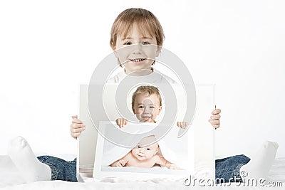 Boy holding his baby photos