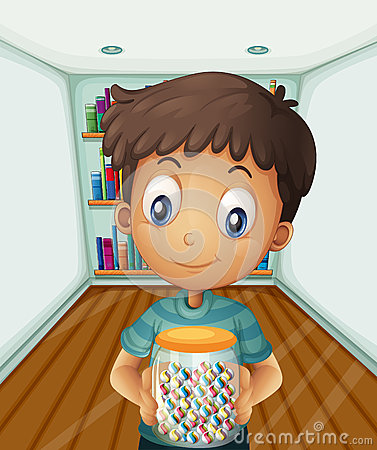 A boy holding a jar of candies in front of the bookshelves