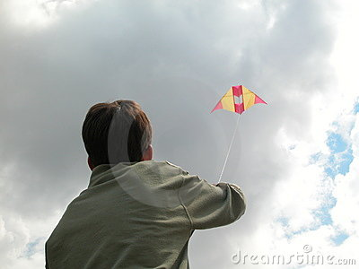 Boy holding a kite soaring, goal dream sky