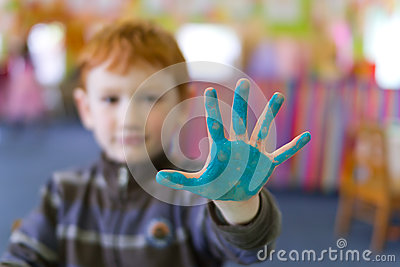 Boy holding out painted hand