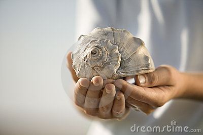 Boy holding seashell.