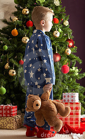 Boy Holding Teddy Bear In Front Of Christmas Tree