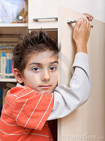 Boy holding on to cupboard door