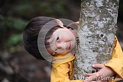 Boy holding a tree