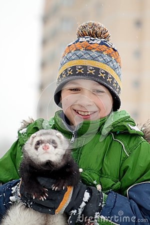 The boy holds a polecat