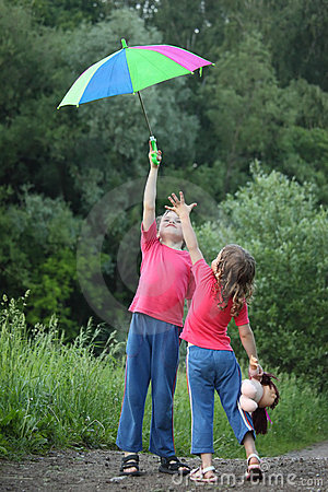 Boy holds umbrella over head, girl pulls to