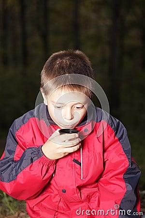 Boy with hot drink in dark forest