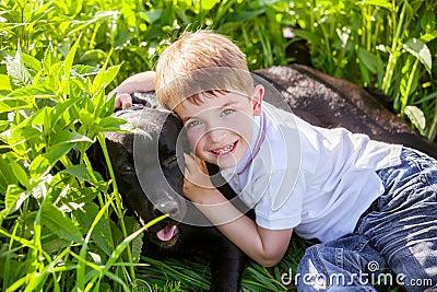 Boy hugging a big dog in an outdoor setting