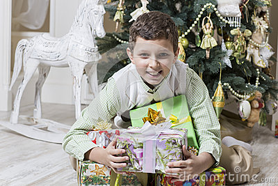 Boy is hugging Christmas gifts