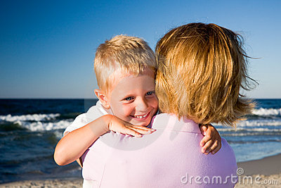 Boy hugging mother on beach