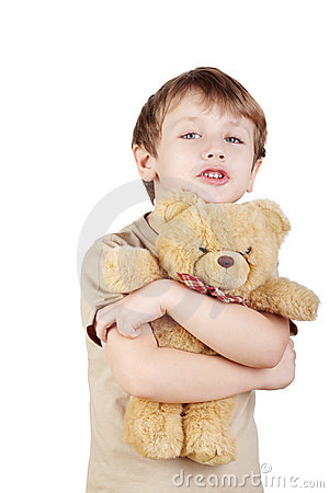 Boy hugs bear-toy and says something.