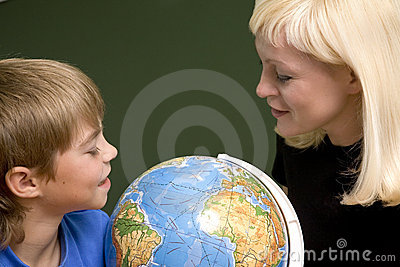 The boy and its mother look at globe