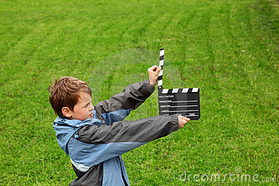 Boy in jacket with cinema clapper board