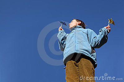 Boy in jacket and pants blowing on pinwheels