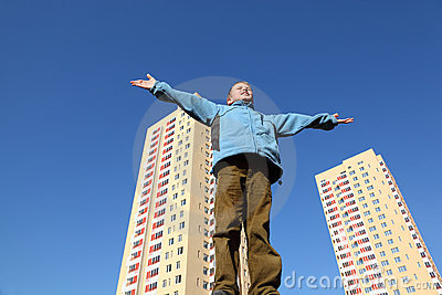 Boy in jacket raises his arms to blue sky