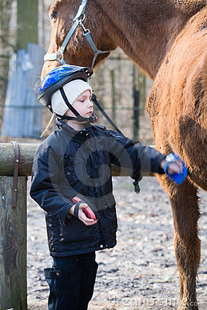 Boy Jockey caring for their horse