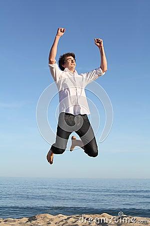 Boy jumping happy on the beach