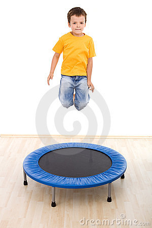 Boy jumping high on trampoline