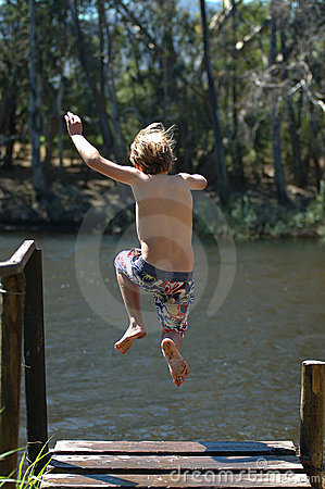 Boy jumping into lake