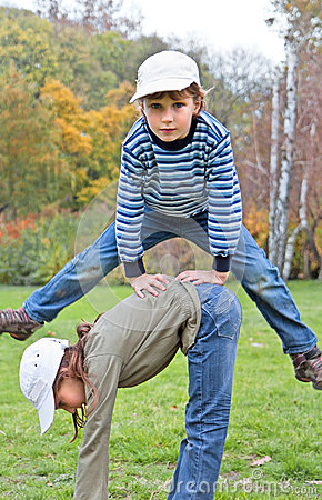 Boy jumping over the girl in autumn park on a grass