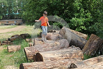 Boy jumping over logs