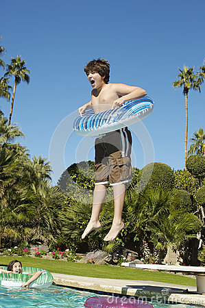 Boy Jumping Into Swimming Pool