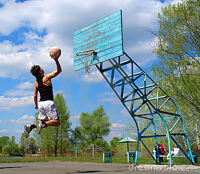 Boy jumps with basketball ball