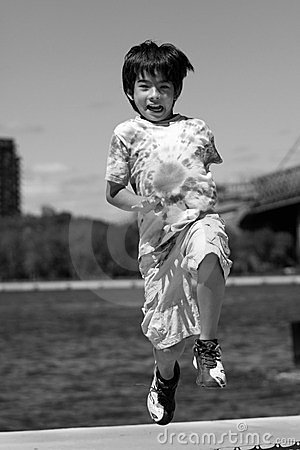 A boy jumps making faces